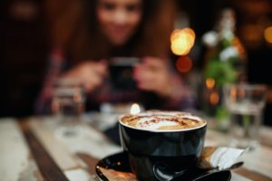 Close up shot of cup of coffee on table at restaurant, with a woman sitting in background. Focus on cup of coffee.