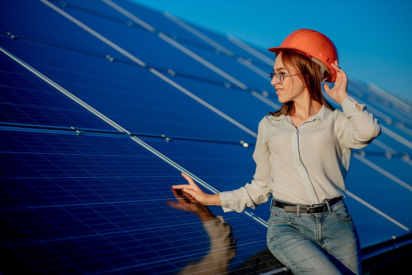 Beautiful young engineer standing near solar panels outdoors, Green Energy Concept.